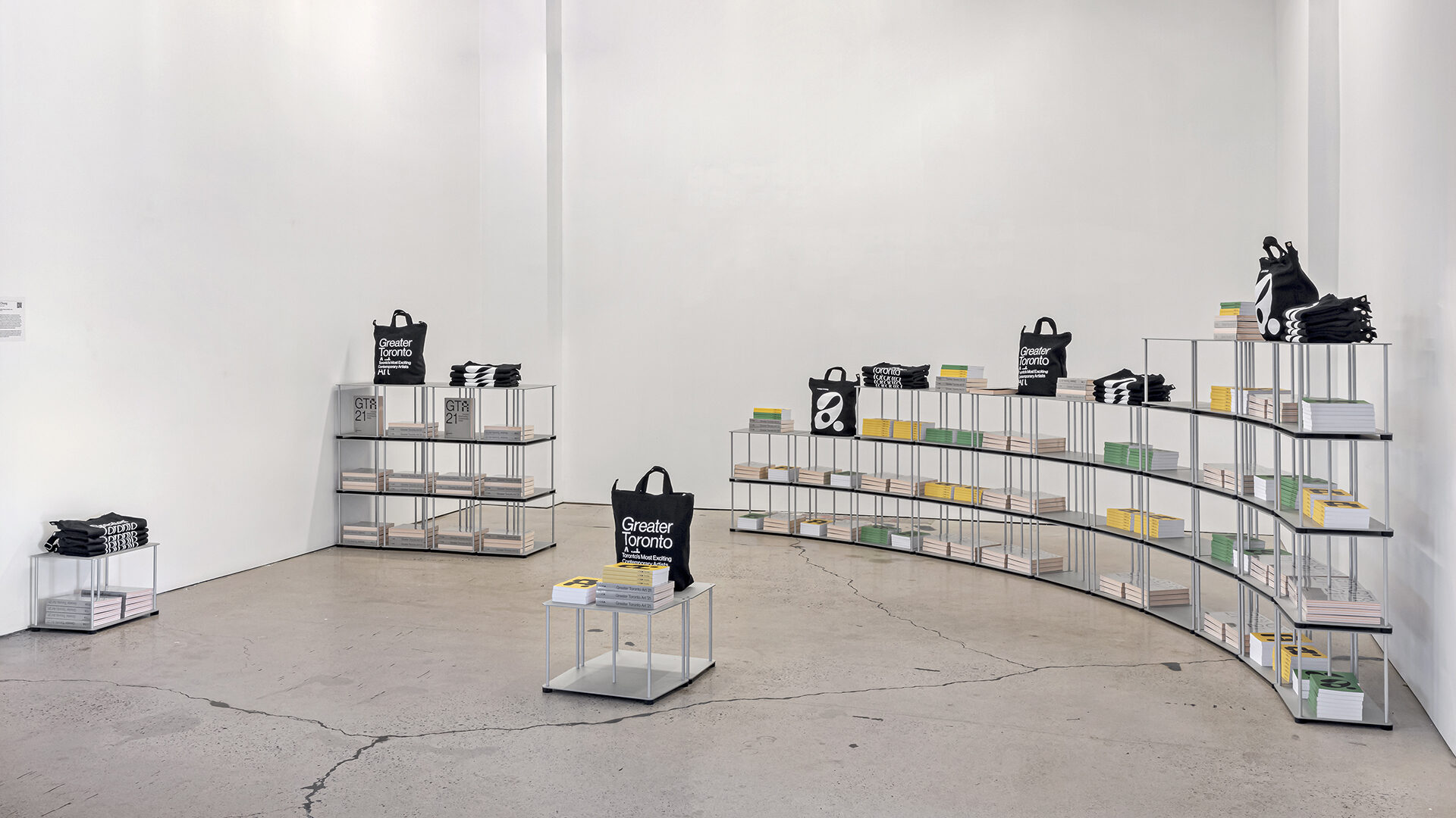 """GTA21 SHop with Tom Chung's """"50 Shelves (study for MOCA)"""" (2021) with GTA21 tote bags, notebooks, and publications"""